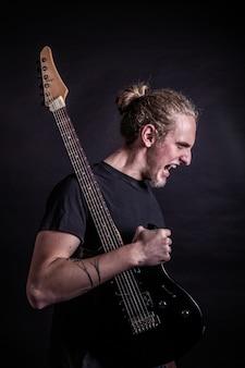 Артист рок-группы кричит с гитарой