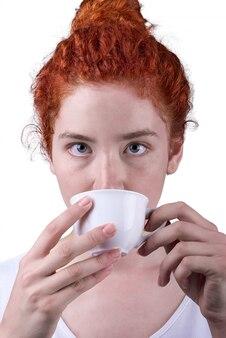 Рыжая девушка пьет кофе