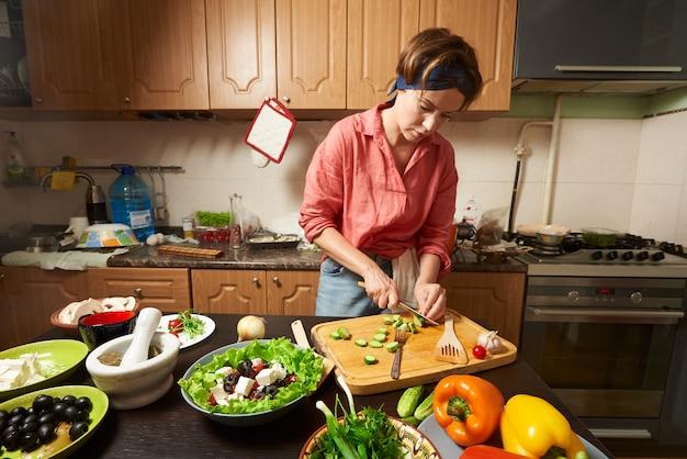 女性が台所でヘルシーサラダを準備します。