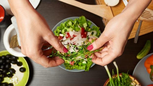 女性の手の健康的なサラダにマイクログリーンを追加する