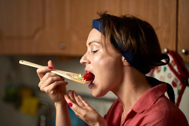 女性が台所でサラダを試飲