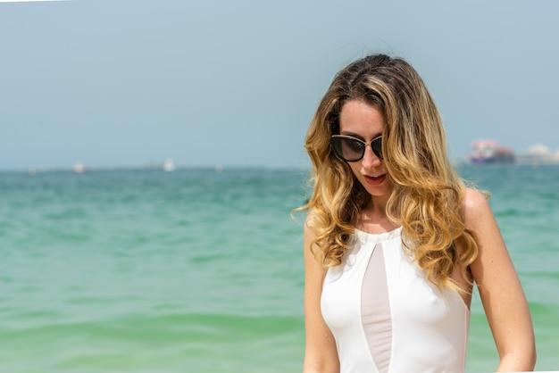 Женщина на пляже дубая в белых купальниках