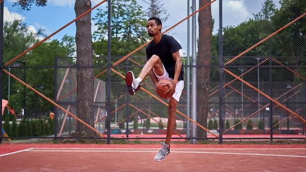 フィールドで遊ぶ黒のバスケットボール選手