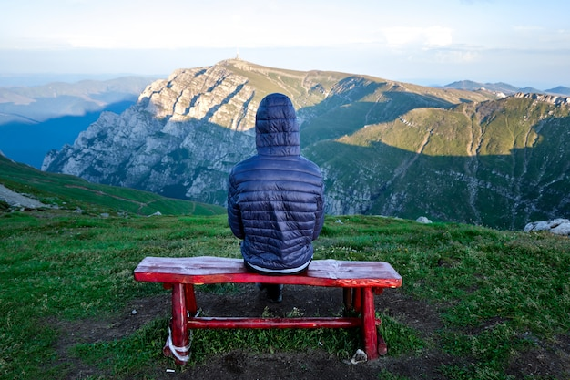 ブチェジ山脈の上に赤い椅子に座って孤独なハイカー男