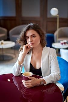 Молодая грустная милая девушка, пить кофе в кафе