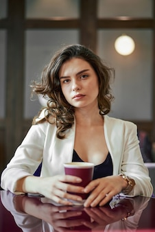 Молодая серьезная девушка, пить кофе в кафе