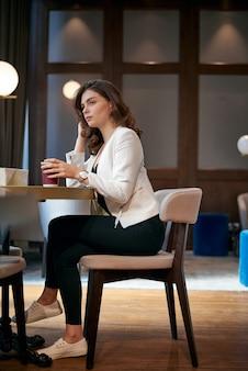 Молодая грустная девушка пьет кофе в кафе