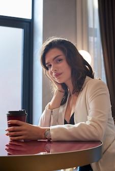 Молодая милая девушка улыбается и пьет кофе в кафе