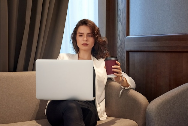 Серьезная молодая девушка работает на ноутбуке и пить кофе