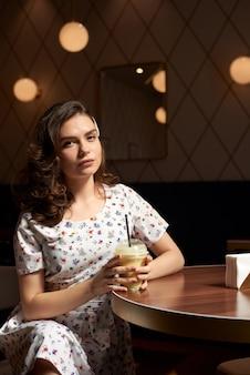 Молодая милая девушка в платье пьет молочный коктейль