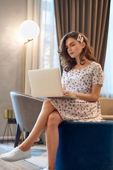 Молодая милая девушка в платье работает на ноутбуке в кафе
