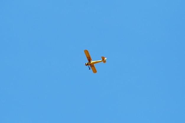 空を飛んでいる黄色の飛行機