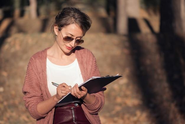 Счастливая усмехаясь женщина работая с бумагами и писать письма