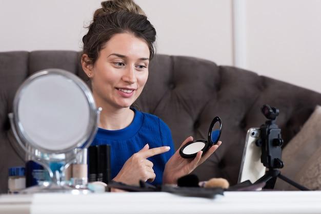 Женщина в голубом платье, представляя макияж влог