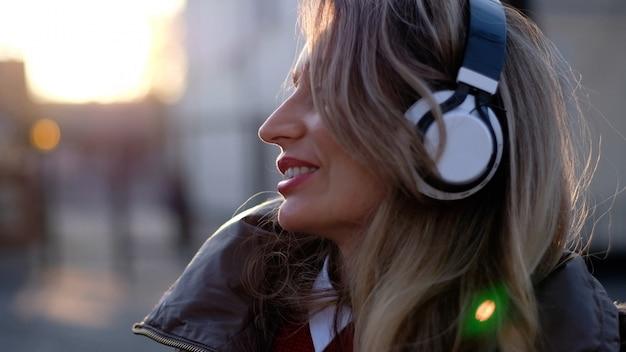 ワイヤレスヘッドフォンで音楽を聞いて幸せな女