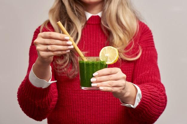 Женщина, держащая свежий шпинат зеленый коктейль с бамбуковой соломой