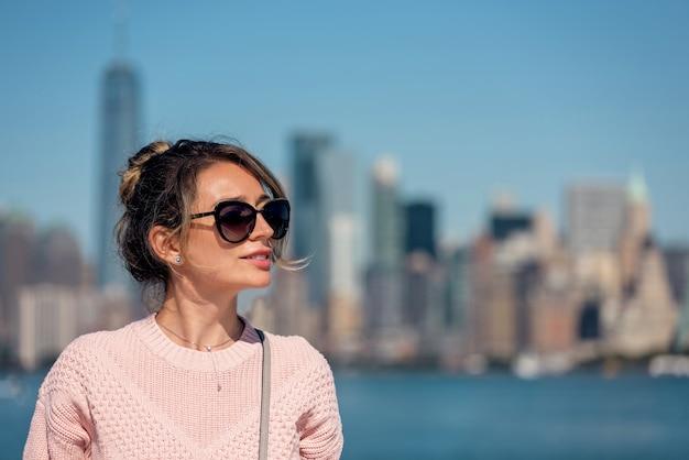 ニューヨークでポーズをとるピンクのセーターの女性