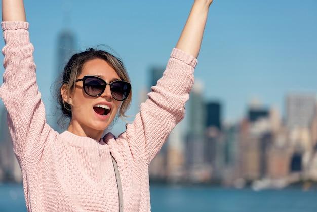Женщина в розовом свитере позирует в нью-йорке