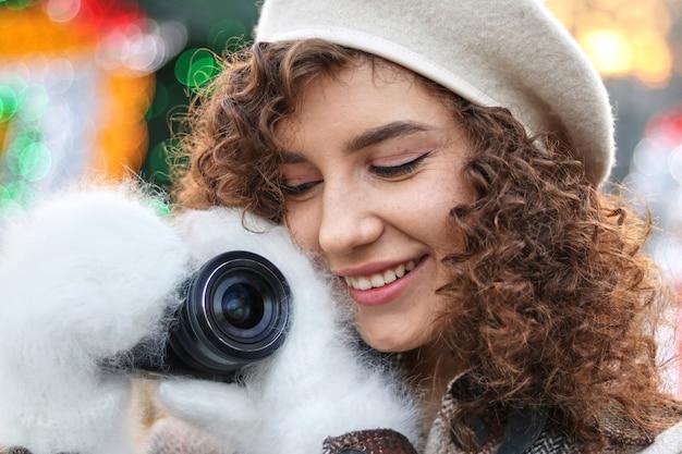カメラで写真を撮るかわいい巻き毛の女の子