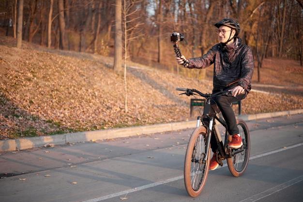 Молодой велосипедист влоге в парке с велосипедом