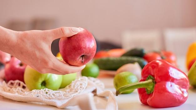 テーブルの上に他の果物と赤いリンゴを保持している女性