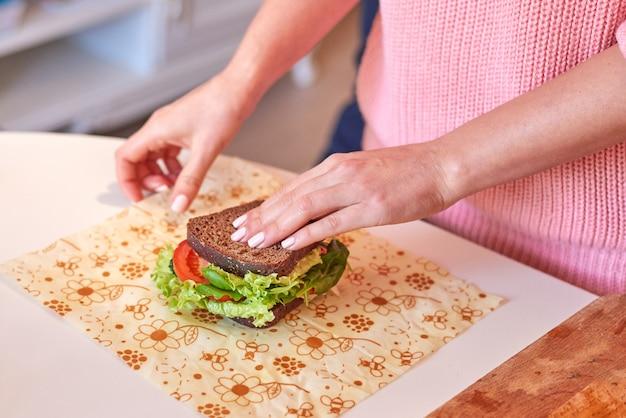 Женщина, завернуть здоровый бутерброд в пчелиный воск