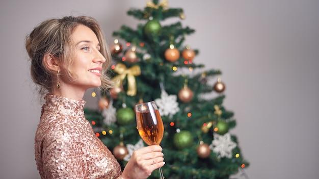 クリスマスツリーとシャンパンのグラスを保持している女性