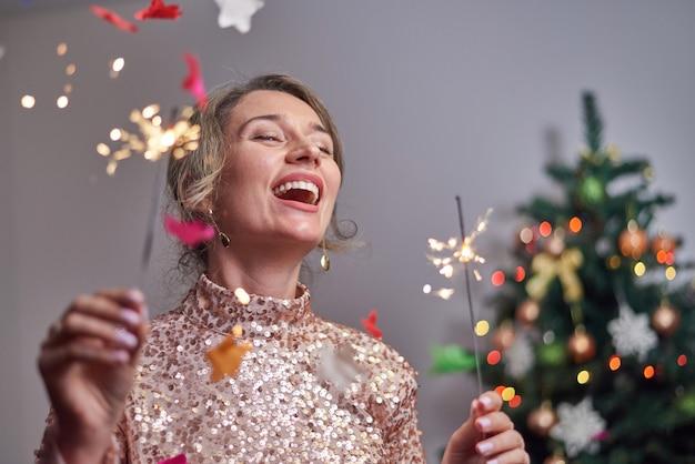 クリスマスツリーと花火に笑みを浮かべて女性