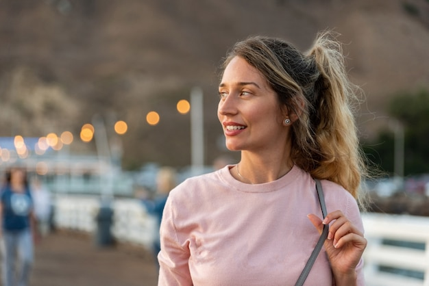 Счастливая белокурая женщина на пляже лос-анджелеса