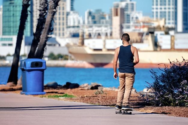 Человек катается на коньках в парке с морем и городом сан-диего