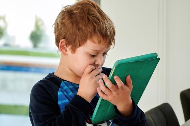 赤毛の子供男の子がタブレットでゲームをプレイ