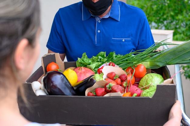 Доставка человек в маске и держит коробку с овощами