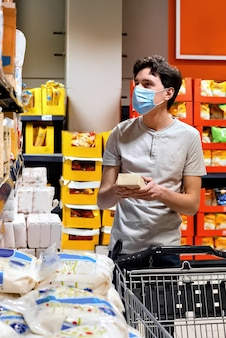 Молодой человек с маской, глядя на закуски в супермаркете