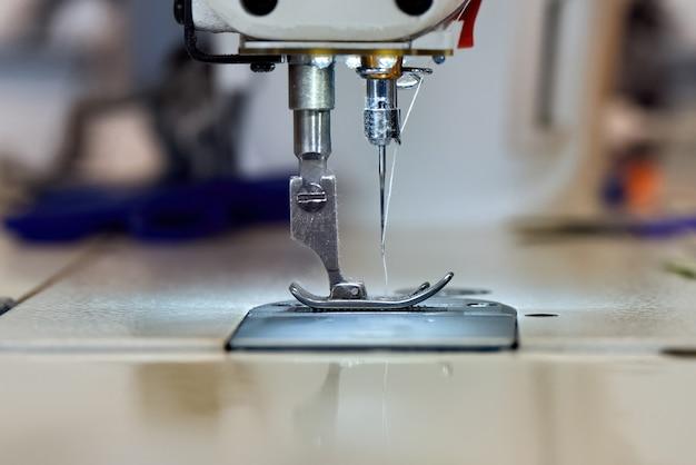 Швейная машина и белая нить крупным планом