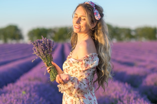 日没で夏のドレスを着てラベンダー畑の女性