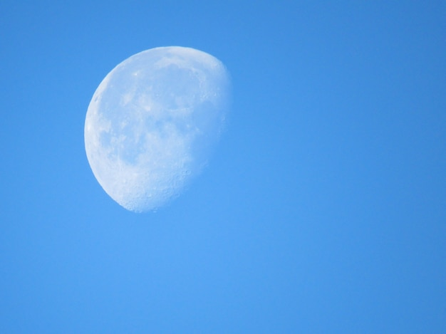 大きな白い月が青空の上を閉じる