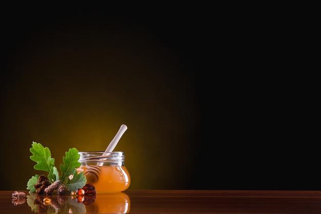 На столе стеклянная банка с медом. мед капает с деревянной ложки. рядом с берегами лежат камни янтаря, ветка дуба, сосновые почки