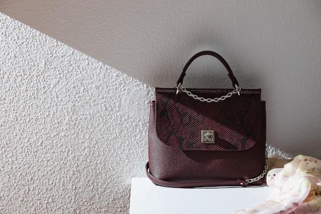 Женская сумка на столе на фоне серой фактурной штукатурки.