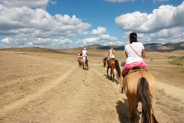 明るい晴れた日に山での乗馬
