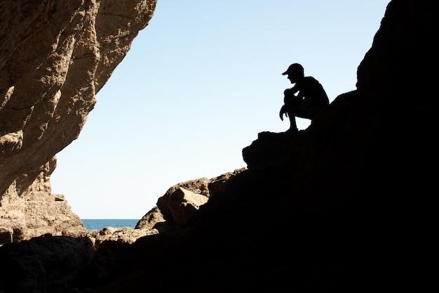 バックライトの岩の上のシルエットの男性