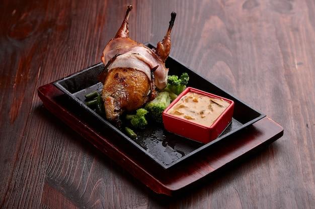食欲をそそる焼き肉料理とソースの暗い木製のテーブル。