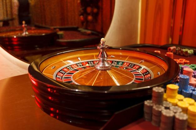 Рулетка, фишки и мяч для казино в интерьере клуба.