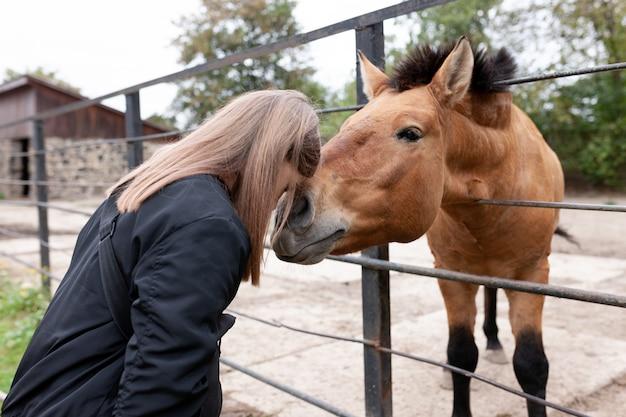 動物園で馬と接触している女の子。