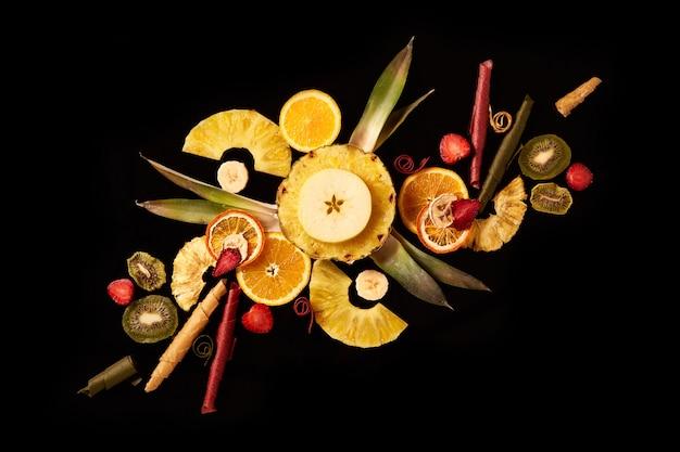 Композиция из свежих и сушеных фруктов и фруктовых кожанных рулетиков на черном фоне