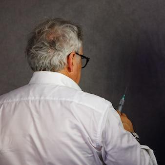 眼鏡をかけた高齢の医師が注射器で薬を収集し、患者に注射する準備をしていました。