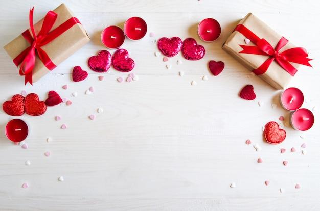 赤いハート、ギフト、キャンドルでバレンタインデーの木製の背景。バレンタインデーのギフト。白い木製の背景