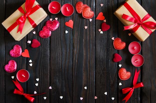 赤いハート、ギフト、キャンドルでバレンタインデーの木製の背景。バレンタインデーのギフト。黒の木製の背景