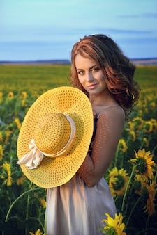 ひまわり畑で帽子をかぶっている若い美しい女性