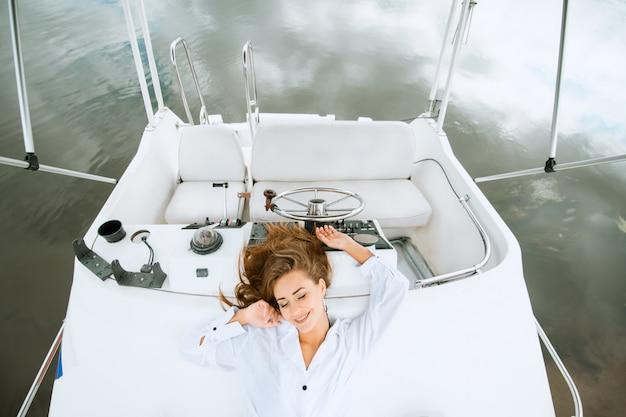 ヨットのデッキに横になっていると海旅行でリラックスを楽しんでいるきれいな女性