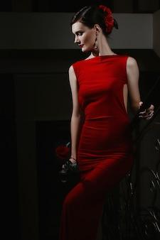 エレガントなドレスと赤いバラを手にした魅力的な官能的な若い女の子は、イベントで歩いています。